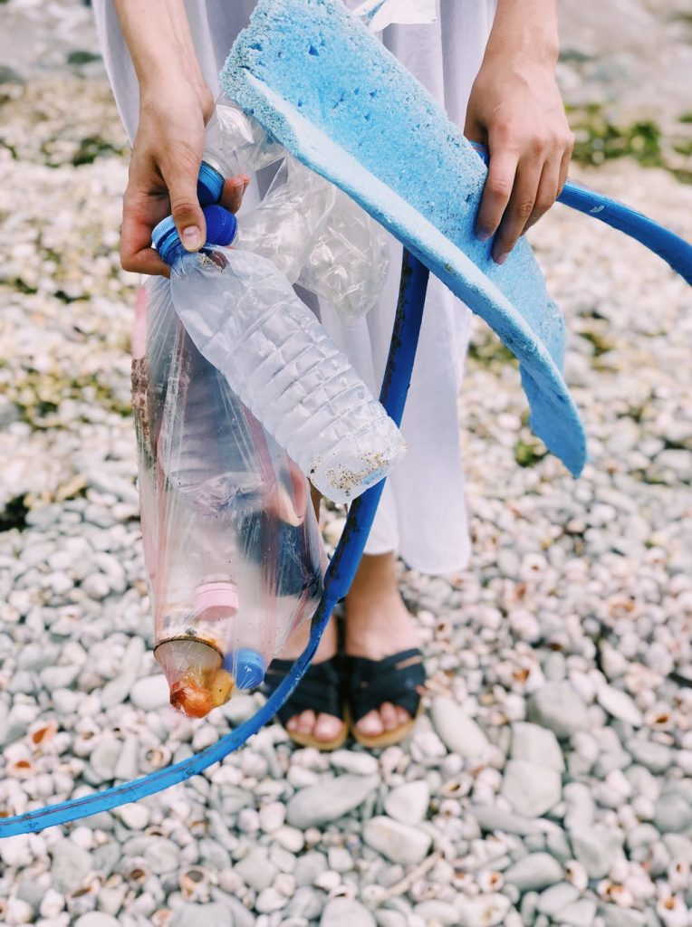 Woman holding plastic waste left on a beach