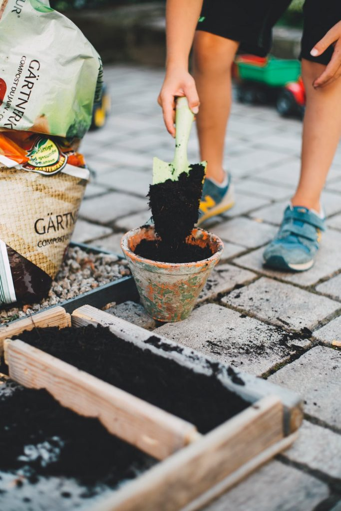 A person putting potting soil into garden boxes and pots