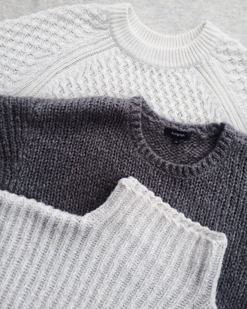 three white and grey wool sweaters
